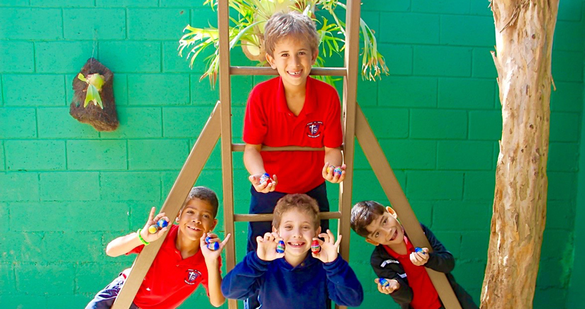 Four elementary-school-aged boys pose in front of a green wall.
