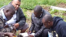 Three men crouch near a soil sample collection site, while a fourth takes notes.