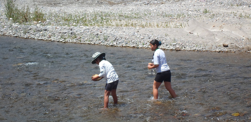 Two girl students wade in a stream and gather water samples.