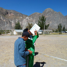 Two students take measurements outdoors.