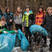 Several student pose together with large trash bags to demonstrate all of the debris they gathered near and in the stream.