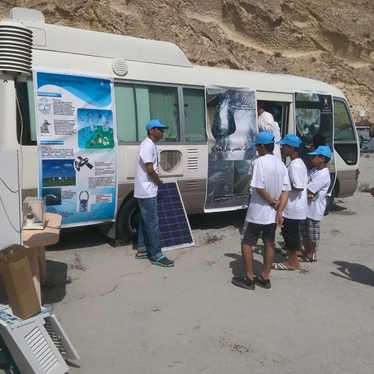 Students listen to a teacher while standing near a RV with science posters affixed to it.