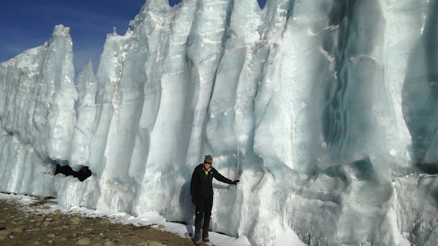 A woman stands next to a glacier.