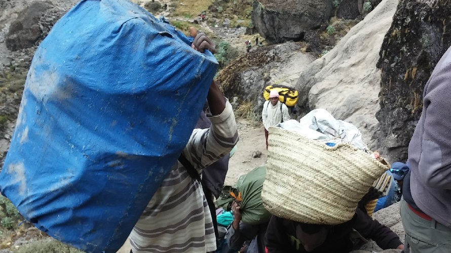 Porters carry bulky and heavy items while climbing a mountain