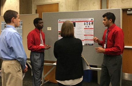People discussing a poster board presentation.