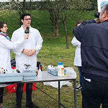A man in a lab coat is interviewed by a woman with a microphone while a man with a camera records the interaction.