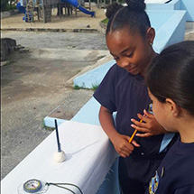 Two students stand and measure solar noon with a compass.