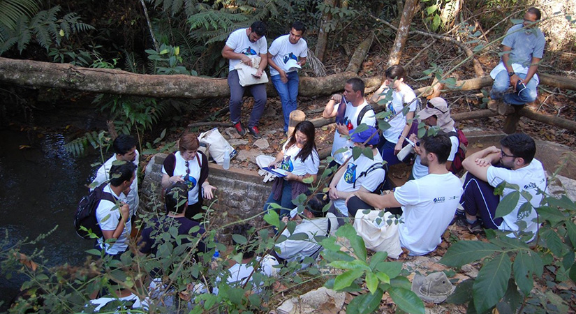 Students and teachers sit near a river.