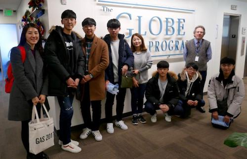 Students and teachers in front of GLOBE sign on a wall.