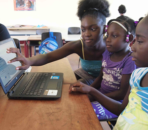 Young children using a laptop.