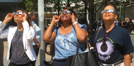 3 women with eclipse glasses.
