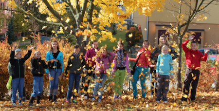 Children throwing yellow leaves into the air.