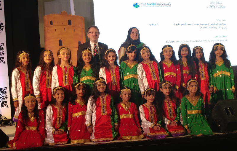Tony in Oman with school children in red and green/