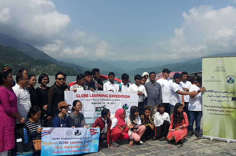 Group with GLOBE banner smiling next to lake Phewa