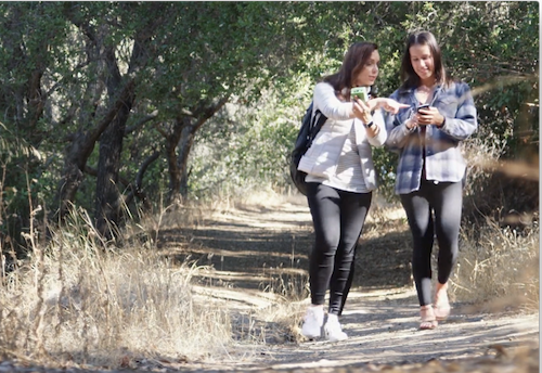 Two girls with cellphones walking in the woods.