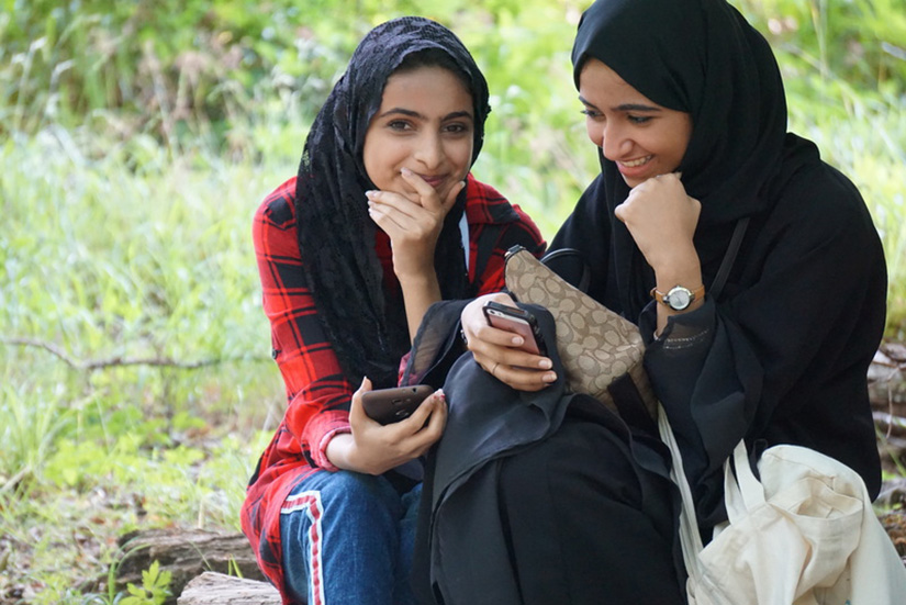 Two girls smile and hold their smart phones.
