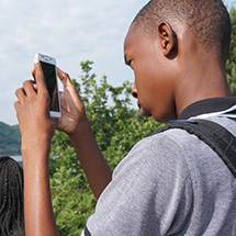 A boy uses his phone to snap a picture with his phone (shooting vertically).