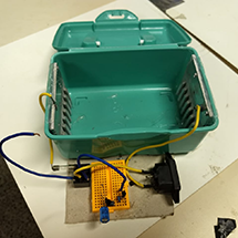 A box with a board and wires.