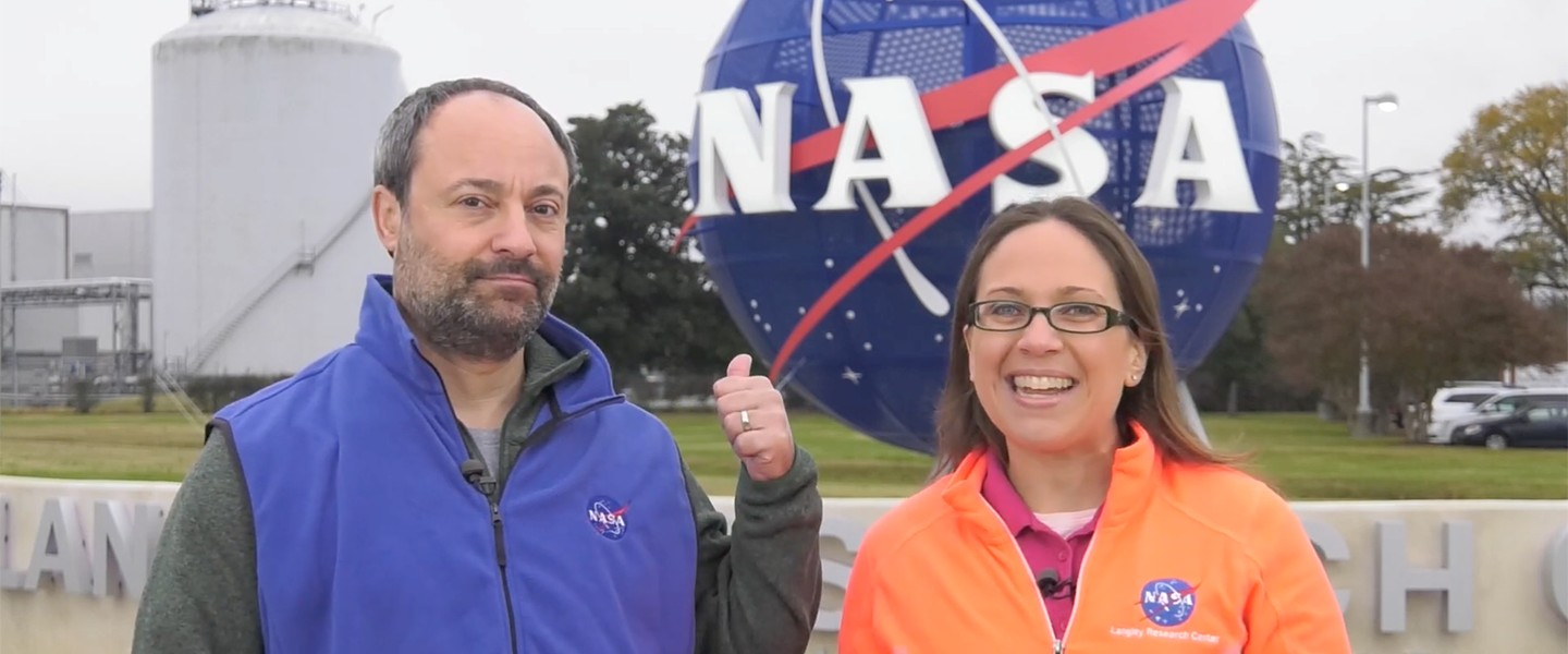 Two people stand out of doors near a NASA sign.