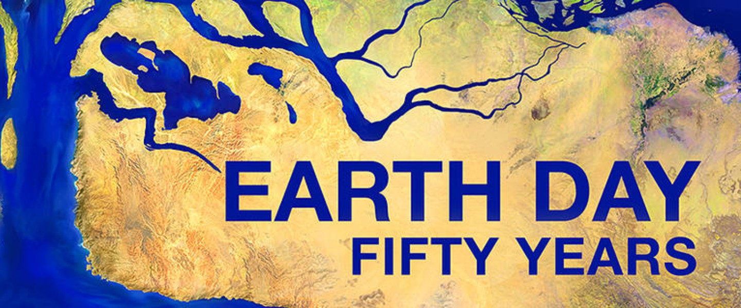 A sign that says Earth Day Fifty years. There is an image of a river that seems to make a shape of a tree.