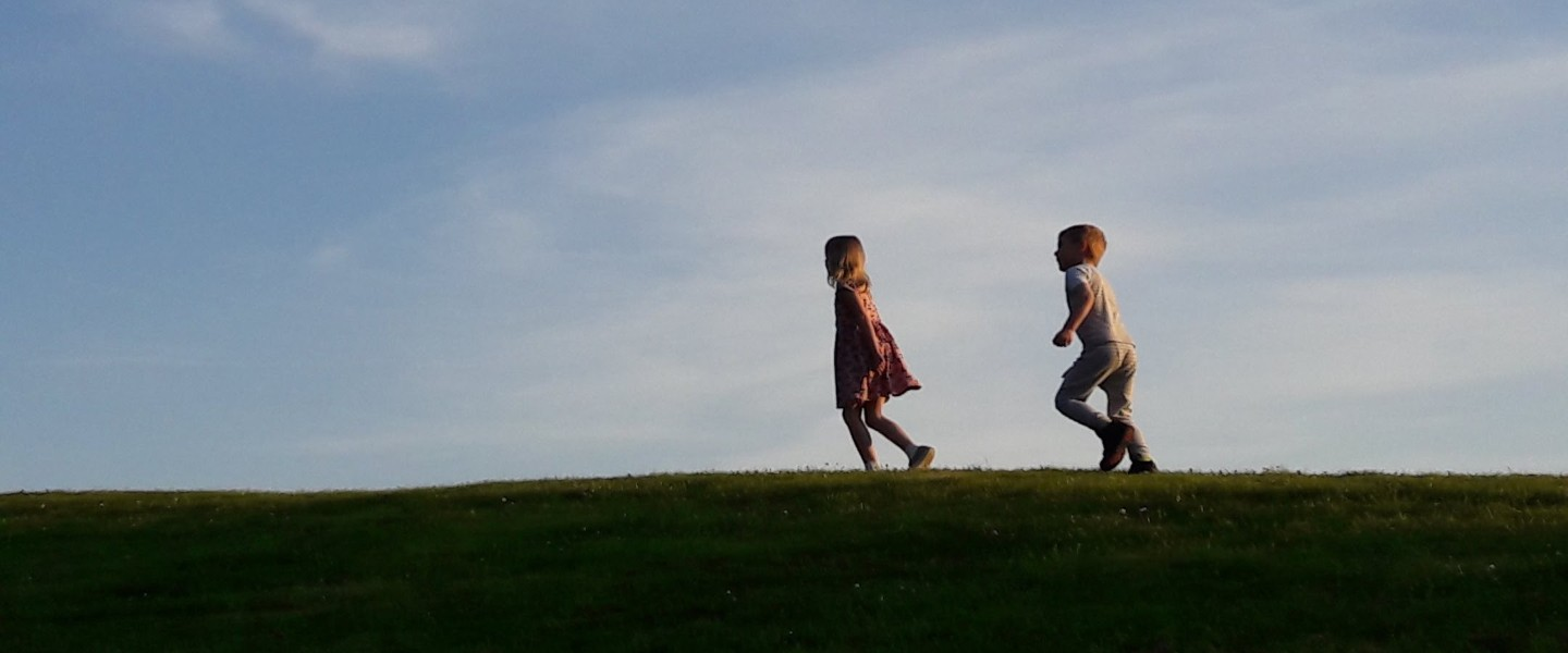 One boy and girl who are walking on a field of grass.