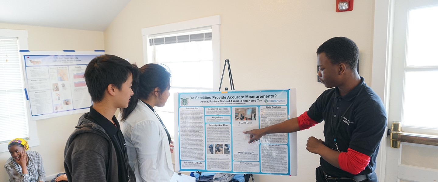 A group of students in front of a science poster.