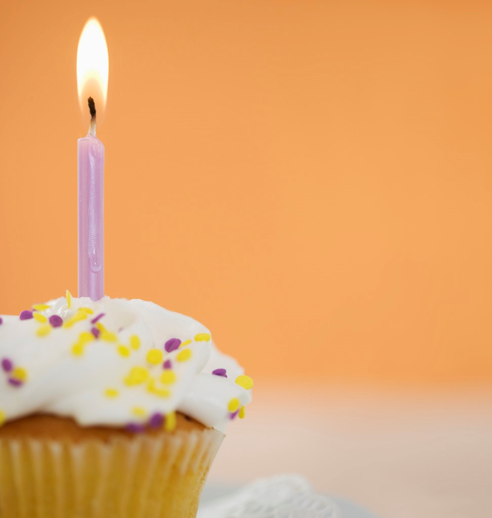 Photo of a lit candle on a cupcake.