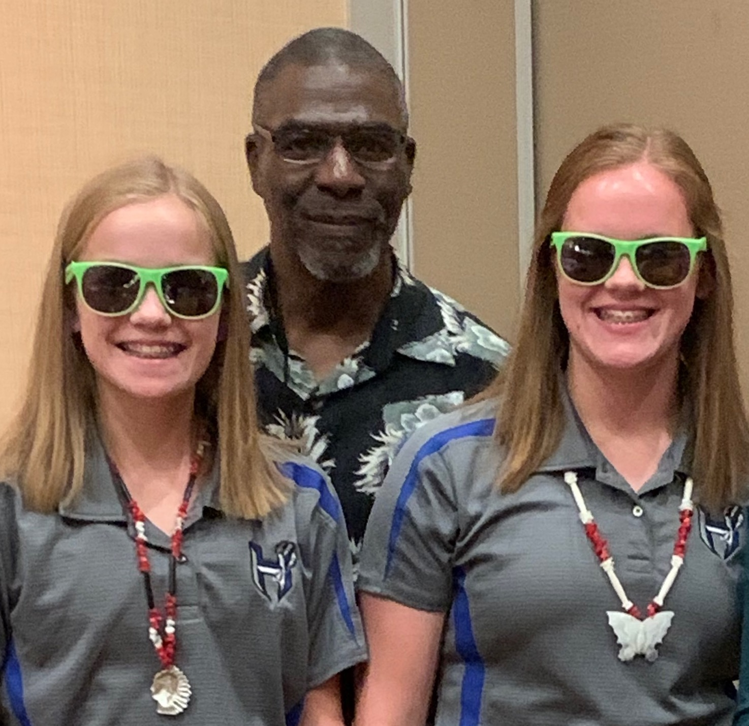 Nate Raynor with two students in lime green sunglasses - the peer choice recognition.