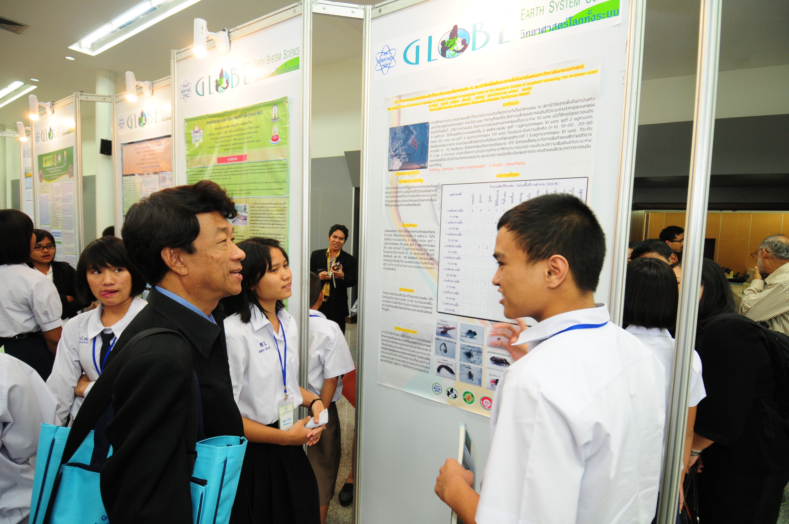 A student discusses their poster with an attendee