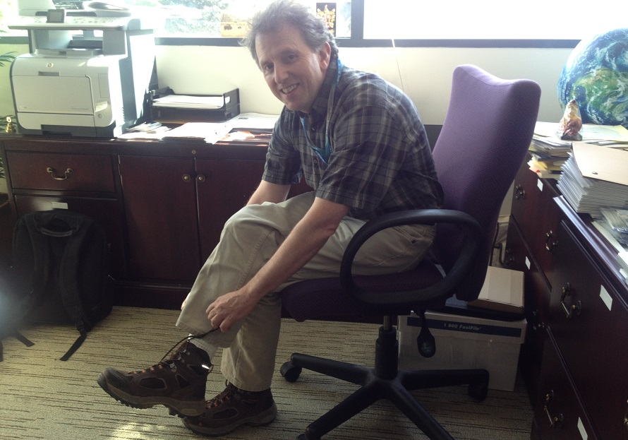 A man ties his shoelaces while sitting in a chair.