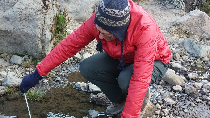 A man takes the temperature of water in a brook.