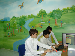 Children on computers in front of a mural