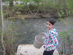 student with bucket near stream